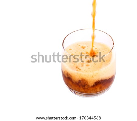 Pouring cola drink into a short glass over white background - stock photo