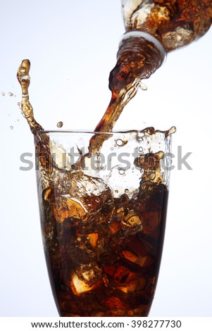 pouring cola drink to glass with ice - stock photo