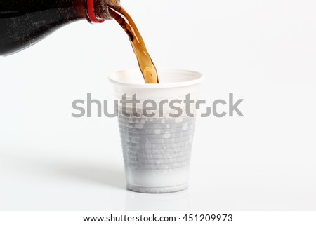 Pouring cola from bottle into plastic cup. Isolated on white background.