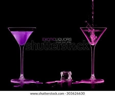 Pouring colorful alcoholic drink in stemmed cocktail glasses and splashing out, close-up isolated on black. Template design with sample text - stock photo