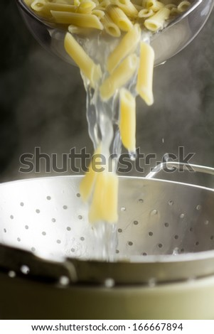 Pouring cooked penne pasta in colander