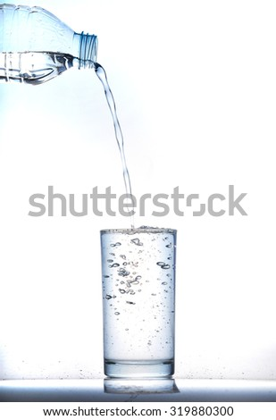 pouring cool water in glass on white background - stock photo