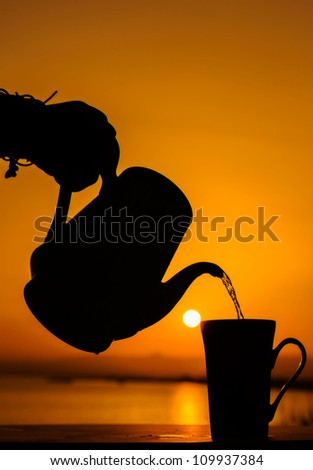Pouring cup of tea with sunset in background.