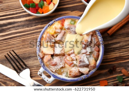 Pouring Custard On Freshly Baked Bread Pudding In Casserole Dish