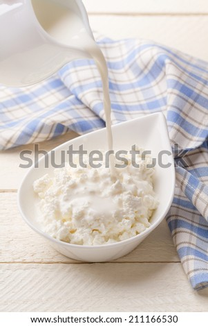 Pouring dairy cream in fresh homemade cottage cheese - stock photo