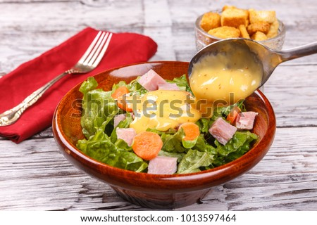 Pouring dressing on a salad.