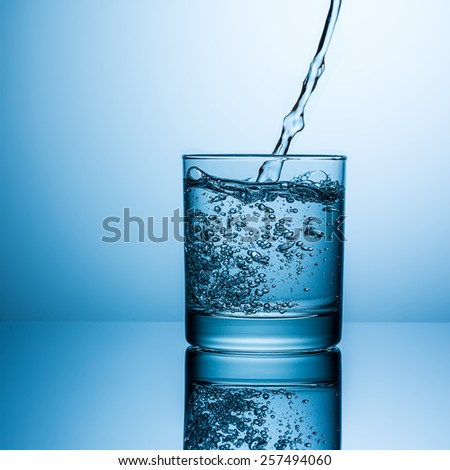 pouring drink water in glass on blue background