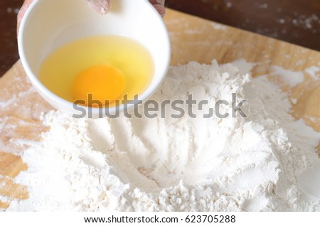 Pouring egg yolk mixing with flour to making bread or cake,bakery cooking