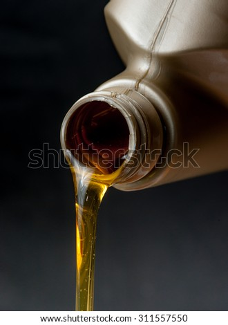 pouring engine oil from its plastic container,dark background - stock photo