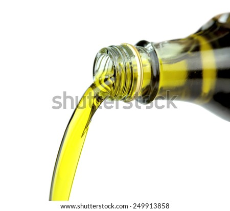 Pouring extra virgin olive oil from glass bottle on white background. - stock photo