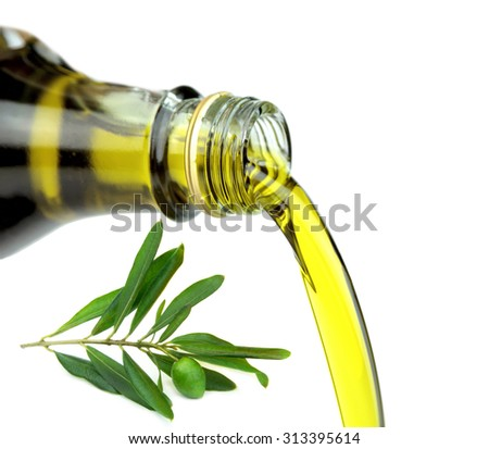 Pouring extra virgin olive oil from glass bottle with green olive branch. - stock photo
