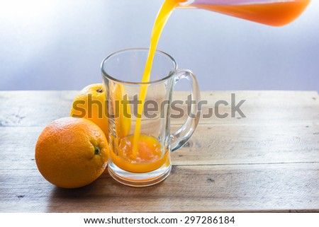 pouring fresh orange juice into a mug - stock photo