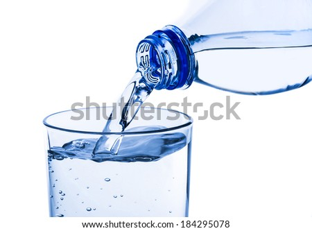 pouring fresh water into the glass from a plastic bottle on white background - stock photo