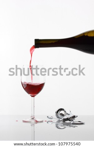 Pouring glass of wine on white with reflection - stock photo