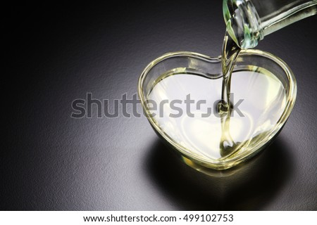 pouring grape seed oil into heart shape container