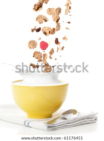 Pouring healthy cereal into a bowl with milk splash - stock photo