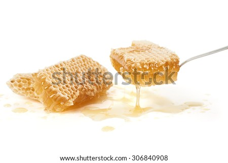 Pouring honey from a spoon over white background                               - stock photo