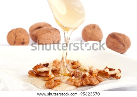 Pouring honey from spoon on the walnut seed