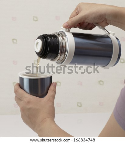 Pouring hot tea from thermos into cup - stock photo