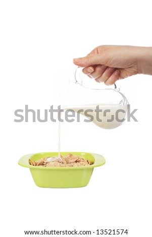 Pouring milk in a cereals bowl isolated on white background. Shallow depth of field
