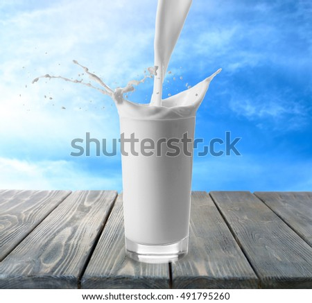 Pouring milk in glass on wooden table with sky background