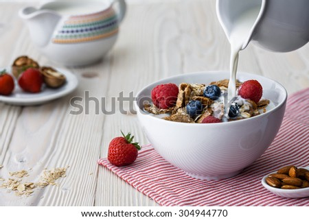 Pouring milk into the bowl with multigrain natural flakes with blueberries and raspberries - stock photo