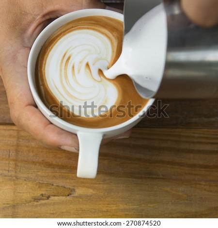 Pouring milk make latte art coffee - stock photo