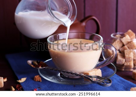 Pouring milk on tea and lump sugar and spices on color wooden planks background - stock photo