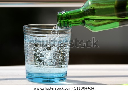 Pouring mineral water in the glass - stock photo