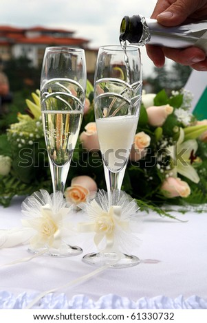 pouring of champagne to the glasses - stock photo