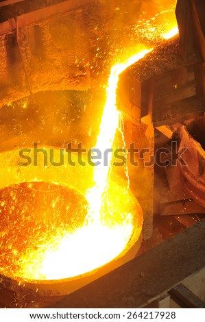 Pouring of hot liquid metal - stock photo