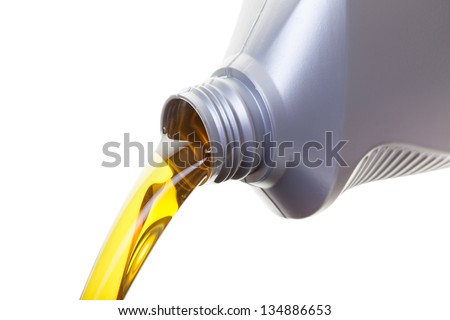Pouring oil from a jug, shot on a whit background