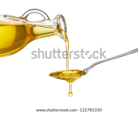 pouring oil on spoon from glass bottle - stock photo