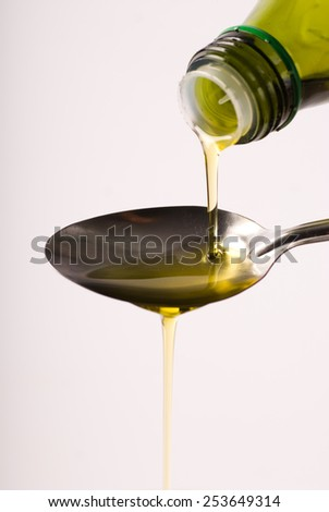 Pouring oil  on spoon. Isolated on white background.