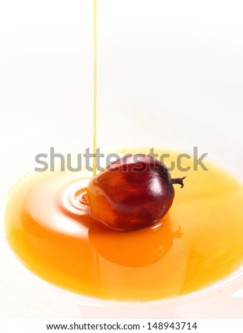 Pouring oil palm fruit cooking oil on white simple background - stock photo