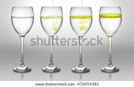 Pouring olive oil into a clear wine glass with alpha and liquid colorizing layer.