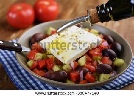 Pouring olive oil into Greek salad - stock photo