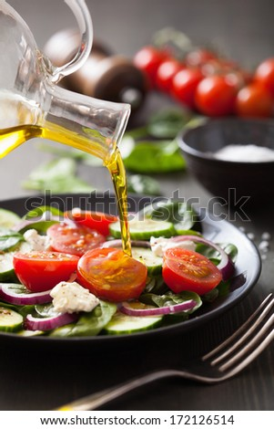 pouring olive oil on salad with tomato and cucumber - stock photo