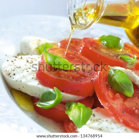 pouring olive oil over tomato & mozzarella - stock photo