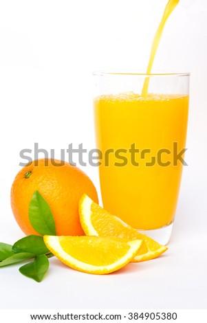 Pouring orange juice and slices of orange isolated on white background - stock photo