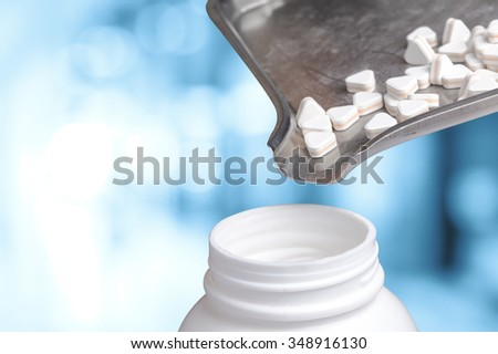 pouring pill in bottle - stock photo