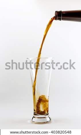 Pouring process of dark stout beer into a beer glass, splashes, drops and froth around glass against white background - stock photo