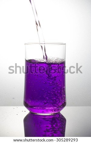 pouring purple drink splash into glass on white background