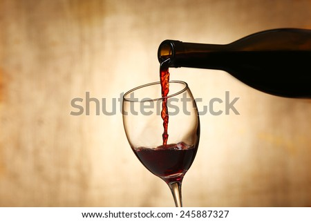 Pouring red wine from bottle into glass on blurred background