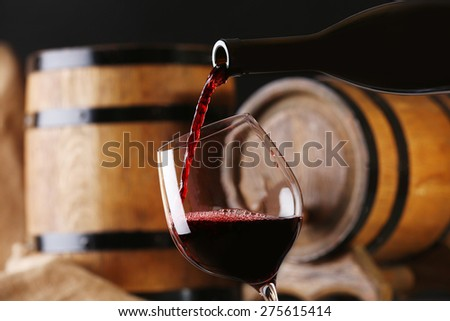 Pouring red wine from bottle into glass with wooden wine casks on background - stock photo