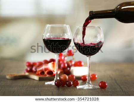 Pouring red wine from bottle into the wineglass - stock photo