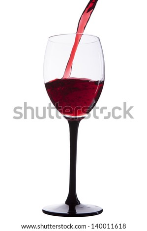 pouring red wine in glass isolated on white background