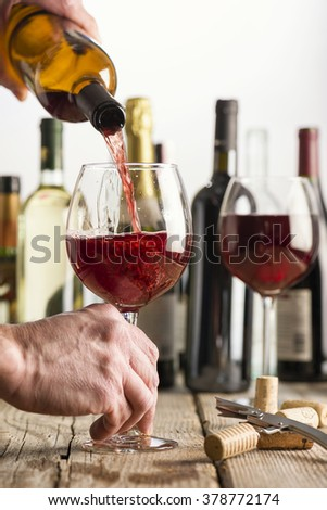 pouring red wine in glass on wooden table near corkscrew and bottle - stock photo