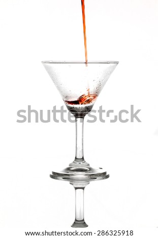 Pouring red wine in to champagne glass isolate on white background