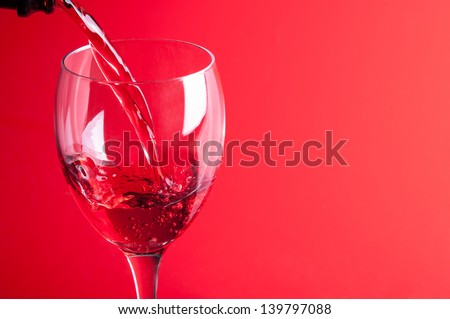 Pouring red wine into a glass on a red background - stock photo